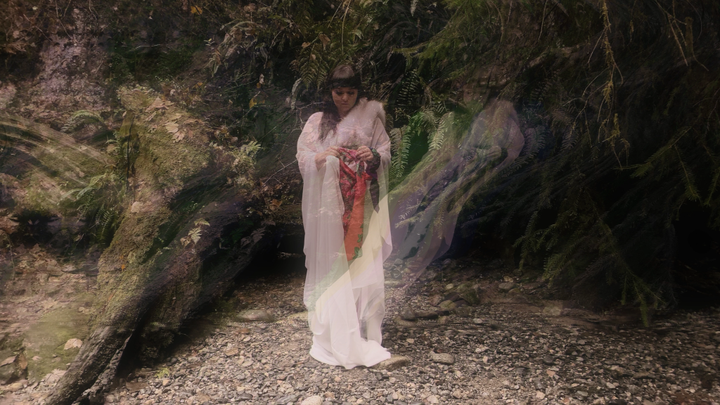 Image of woman in pale pink robe in forest