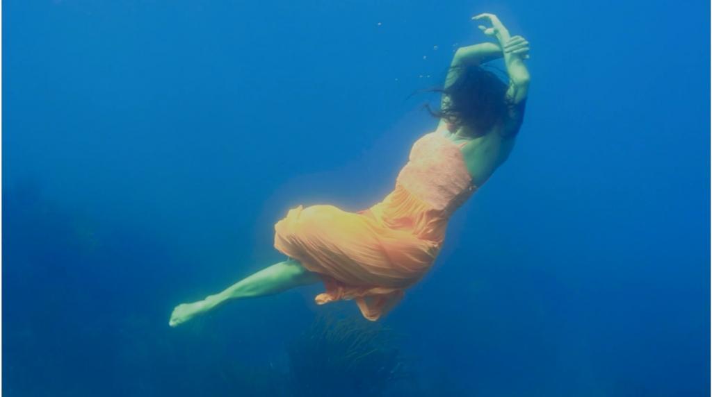 Woman swimming underwater in orange dress