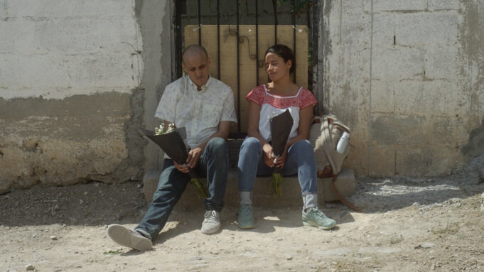 Man and woman sitting on a doorstep in Mexican town
