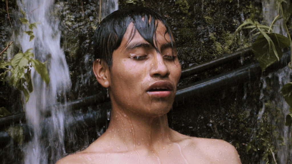 Image of young man under waterfall