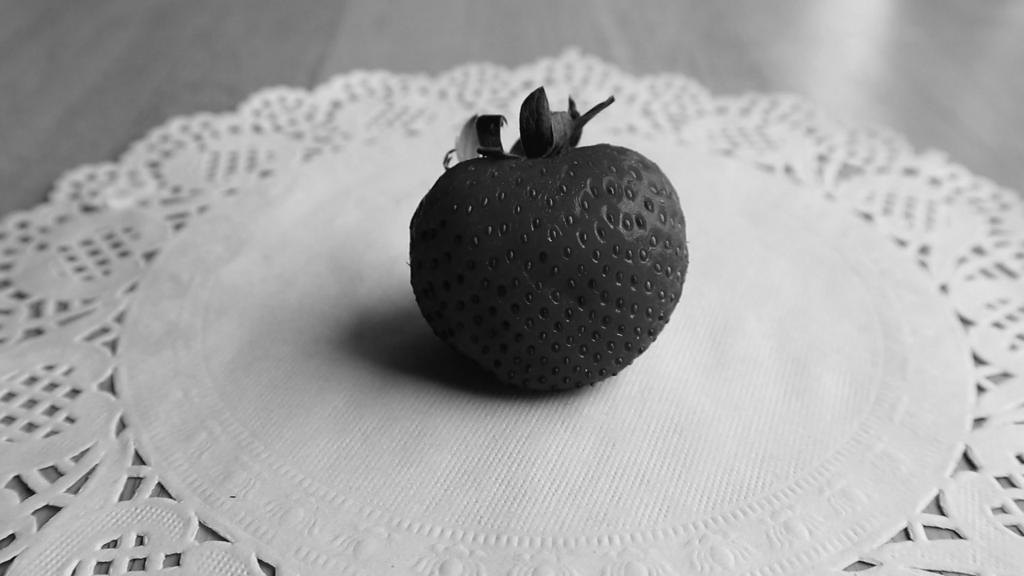 B& W photo of a strawberry on a doily