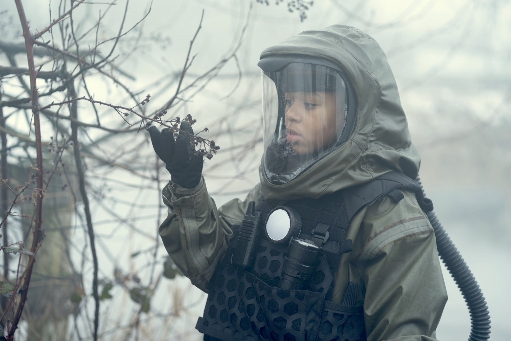 Young girl in spacesuit in wasteland
