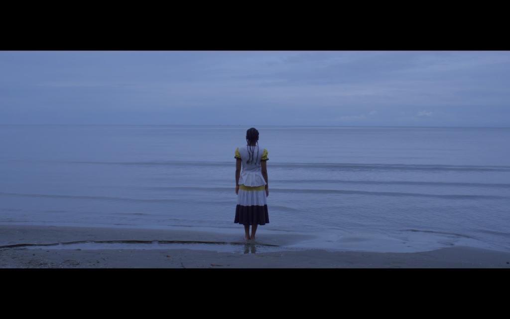 Woman standing near edge of sea