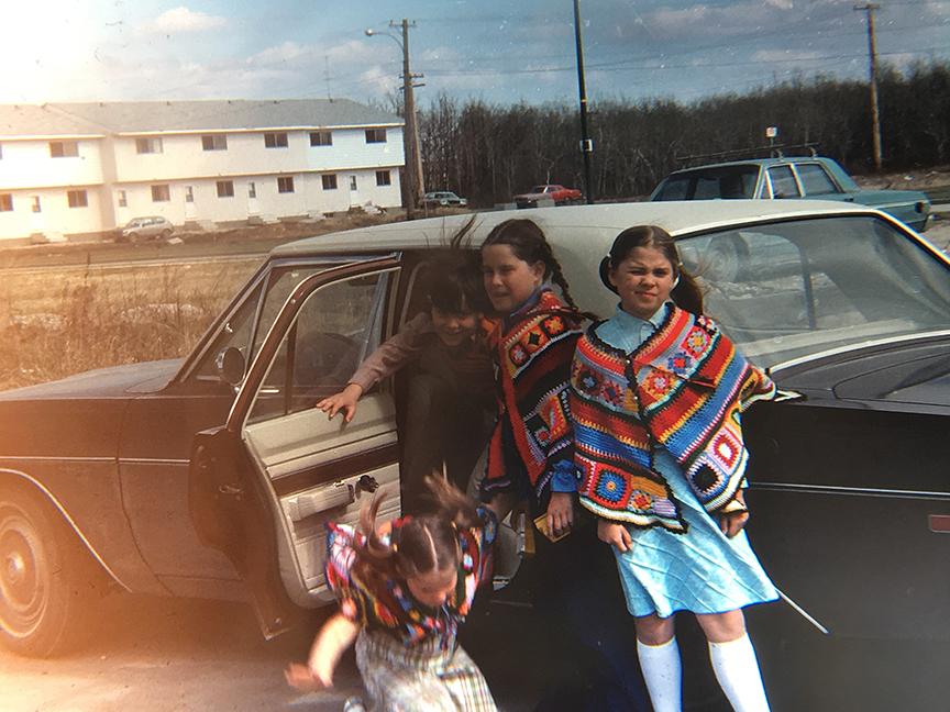Image of three children near family car
