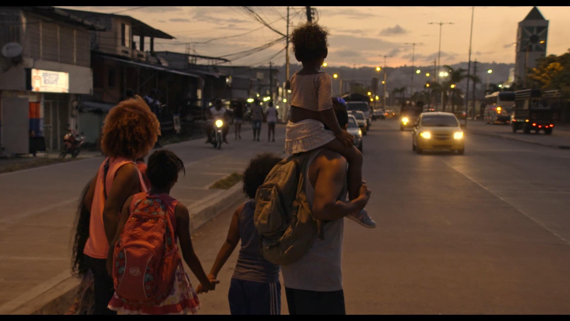 Family walking along city street at sunset